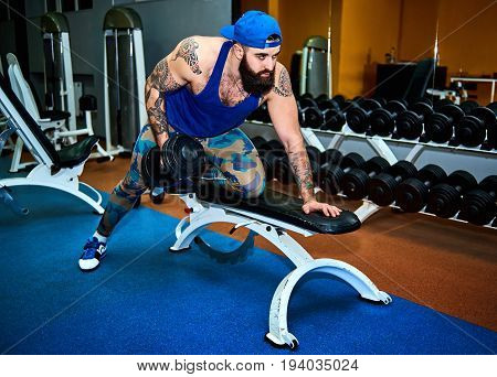Young bearded tattooed man in baseball cap training with dumbbells on the bench in gym. Muscular young man exercising. Full body length portrait