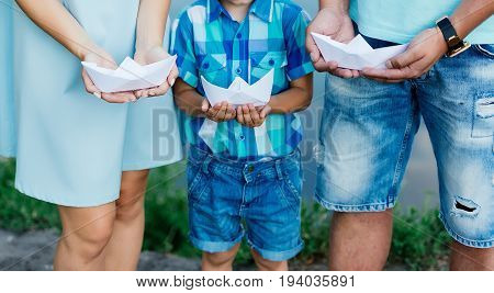 Family in blue clothes holding white paper boats in hands near water outside. Paper ship in father mother and sun hands outdoors on sunny summer day