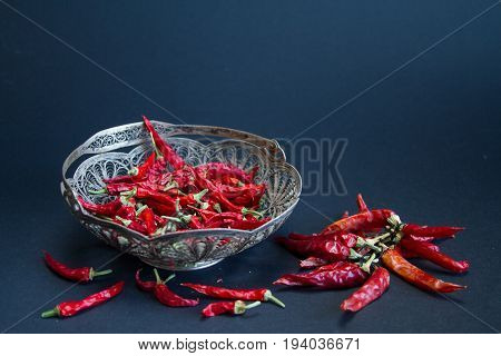 Red Chili pepper in a silver vase on a black background.