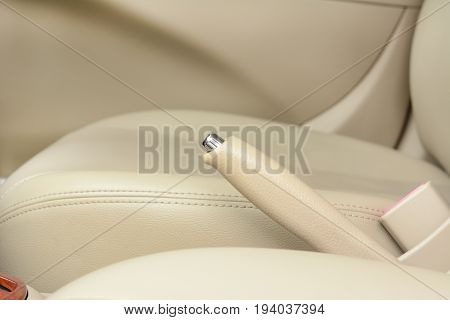 Car hand brake lever near driver seat - beige color