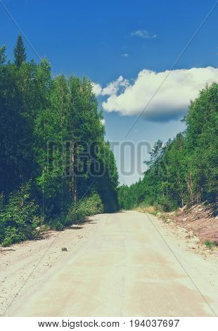 Straight sandy dirt road through the forest in the mountains of northern Karelia (Russia) at sunny summer day. Vintage film effect.