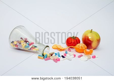 Colorful medical pills in glass containers and in bulk on a white background. Next are vegetables and fruits.