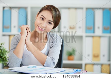 Portrait of smiling Asian business lady at her table looking at camera