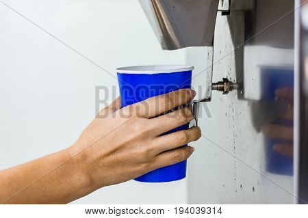 Hand Of Woman Serving Ice Of  Ice Maker Machine