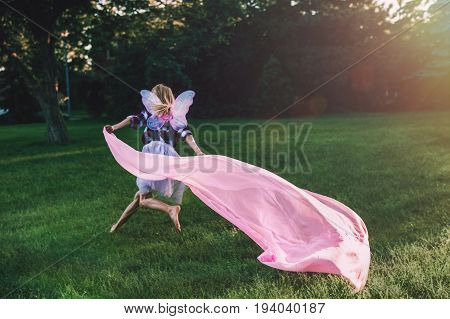 Portrait of running blonde white Caucasian child kid girl with long hair wearing pink fairy wings and tutu tulle skirt holding large piece of fabric happy lifestyle childhood play concept