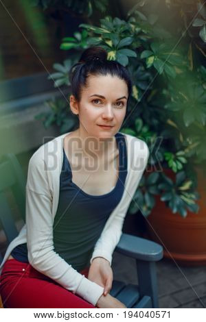 Portrait of sad pensive serious young beautiful white Caucasian brunette woman with dark hair bun and brown eyes sitting on bench in park outside looking in camera