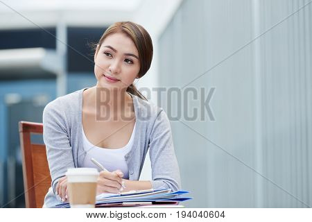 Beautiful young Asian business woman filling documents