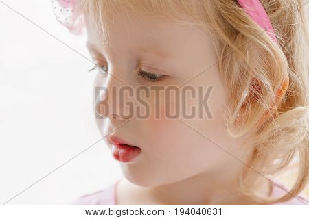 Closeup portrait of cute adorable blonde white Caucasian smiling baby girl with large blue eyes wearing pink headband looking away
