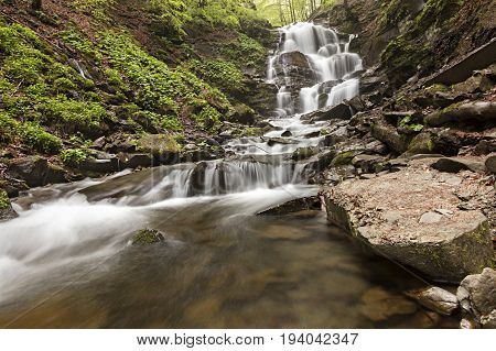 A large boulder lies at the foot of a waterfall in the Carpathian mountainsA large boulder washed early in the morning at the foot of a waterfall in the Carpathian Mountains