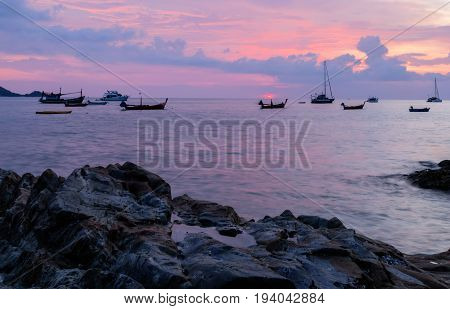 fishing boat and sailing yacht with sunset on the beach in phuket Thailand