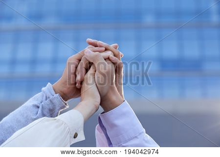 Business coworkers clasping their hands together to show unity