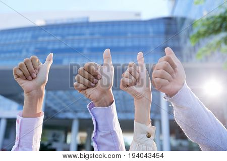 Four hands of business people showing thumbs-up to encourage