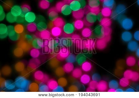 Color light blurred on black background unfocused. Christmas or other holiday decorations