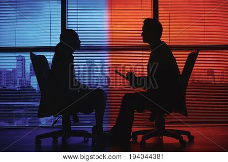 Silhouttes of business lady having job interview, background is in red and blue colors
