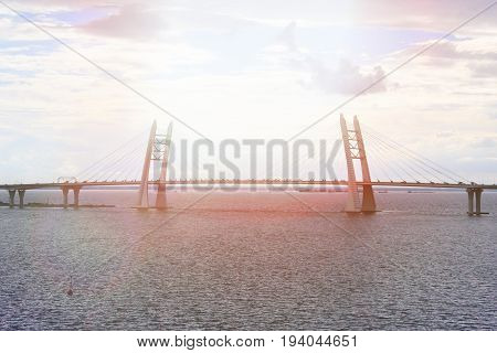 View of the cable-stayed bridge across the Strait on the background of sea and blue sky, summer evening, solar flare, beam.