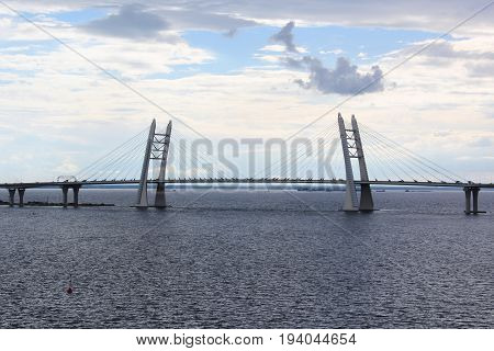 View of the cable-stayed bridge across the Strait on the background of sea and blue sky, summer evening