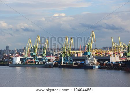 St. Petersburg, Russia - June 25 2017: The cargo port. Containers with goods are loaded / unloaded on a commercial vessel using a crane in the harbor of the city. Summer. Business transport concept