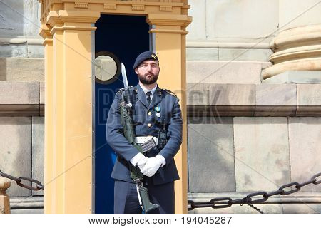 Stockholm, Sweden- 27 Jun 2017: The Royal Swedish soldier - guardsman with a black beard in a modern uniform with a gun on the guard of the Royal Palace in the capital of the country.