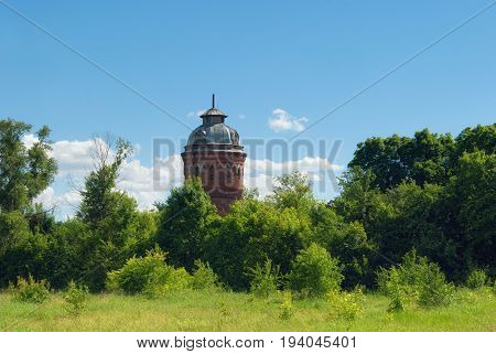 Building Of The Old Russian Abandoned Water Tower Resembling A Chapel Standing In The Countryside