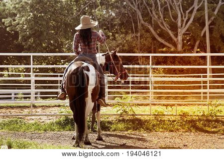Pretty Asian woman cowgirl riding a horse outdoors in a farm for relax.