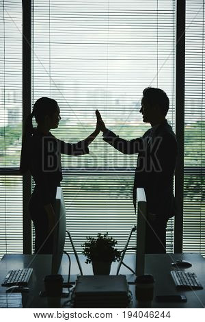 Happy business partners giving each other high five, silhouettes against big window