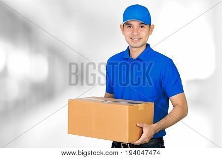 Asian deliveryman carrying a cardboard parcel box on blur white gray background