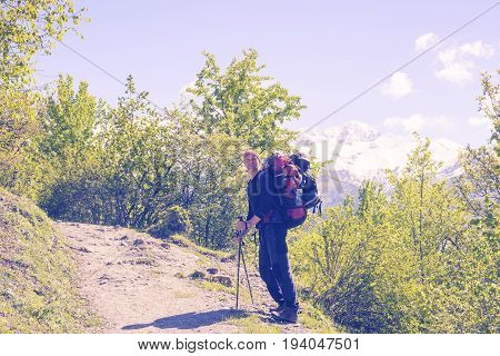 Traveler With Big Backpack Resting During A Difficult Climb