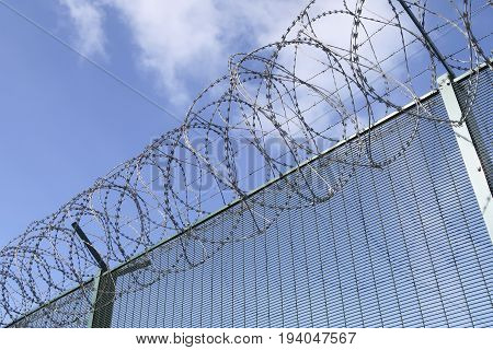 Part of a barbwired fence on a blue sky with clouds from a low angle view