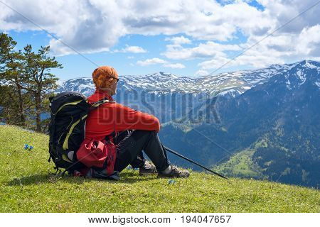 Man Adventurer Sits On The Alpine Meadow Among The Wildflowers