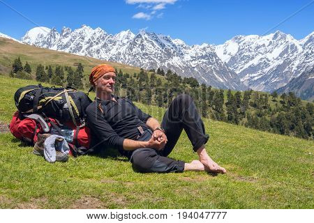 Tired Man Traveler Relaxed, Lying On The Alpine Meadow