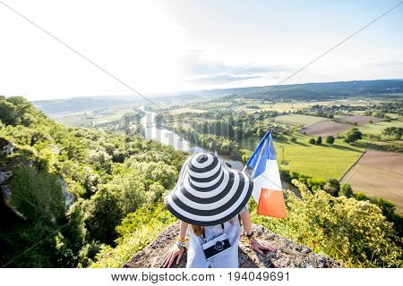 Young woman tourist i hat with french flag enjoying sunset view on the beautiful landscape with Dordogne river in France