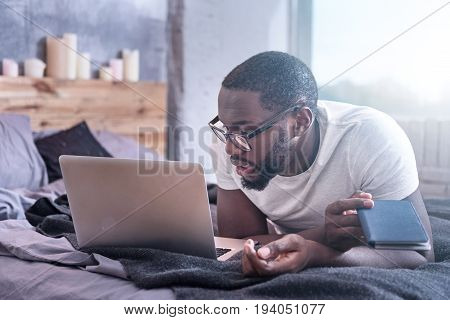 Full of attention. Gifted smart involved African American man lying on the bed at home while using modern gadget and working