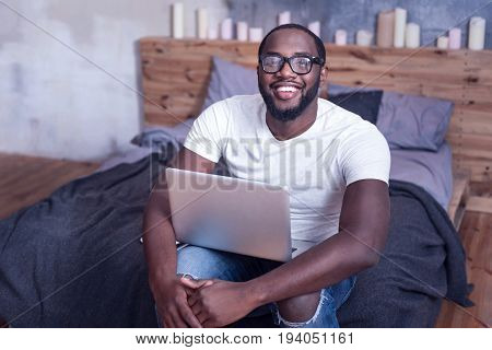 Full of positive emotions. Smart crafty charming African American man sitting on the bed at home while using laptop and working