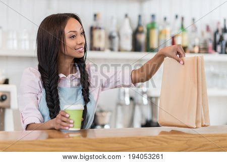 smiling afro american waitress holding coffee to go and take away food in hands