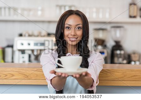 attractive african american waitress in apron holding coffee cup and looking at camera at cafe