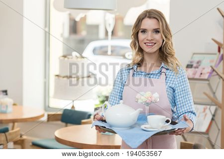 beautiful blonde waitress in apron holding tray with tea and cookies at cafe