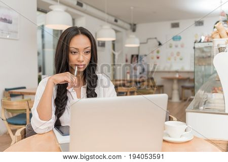 young pensive african american businesswoman using laptop while sitting at cafe