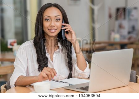 young beautiful african american businesswoman talking on smartphone while sitting near laptop at cafe