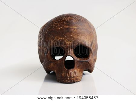 A model of a human skull in the form of a candlestick on a white background