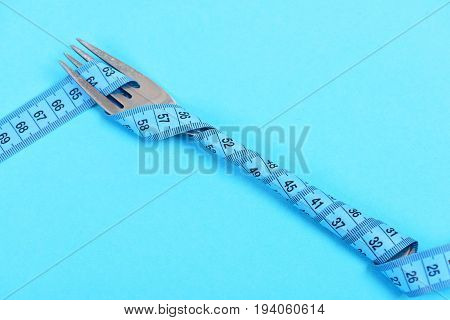 Fork With Turquoise Blue Measuring Tape Isolated On Cyan Background