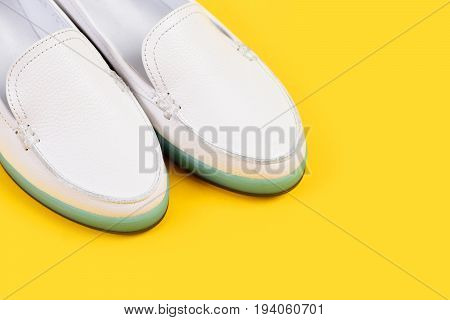Summer fashion and casual lifestyle concept. Low heel footwear in sports style. Moccasins for women in white color. Pair of female leather shoes isolated on yellow background close up and copy space