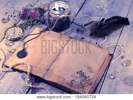Open diary with old clock, black candle, quill and medallion on planks. Vintage romantic concept. Mystic and occult still life