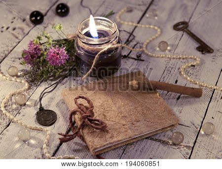 Black candle with diary, medallion, key and mystic objects on planks. Mystic and occult still life, vintage romantic background