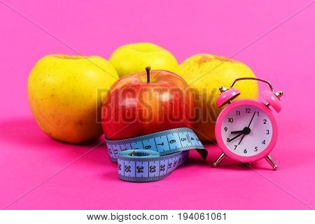 Alarm Clock In Pink Color And Apples Wrapped With Ruler