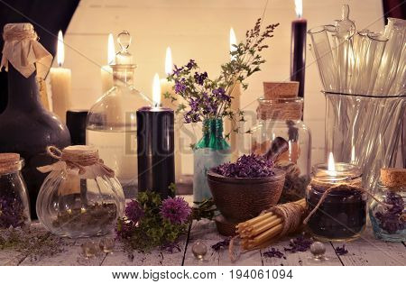 Glass jars and bottles with black candles and healing herbs on the alchemical table. Alternative medicine, old pharmaceutic and homeopathic concept. Mystic and occult still life, vintage background