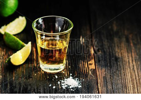 Golden tequila shots with sea salt juicy lime on vintage black wooden board toned selective focus copy space.