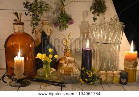 Alchemical or pharmaceutical still life with jars, healing herbs and burning candles. Alternative medicine, old pharmaceutic and homeopathic concept. Mystic and occult still life, vintage background