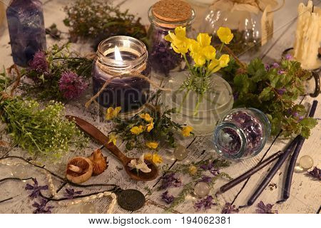 Black candle, flowers, healing herbs and mystic objects on the planks. Alternative medicine, old pharmaceutic and homeopathic concept. Mystic and occult still life, vintage medical background