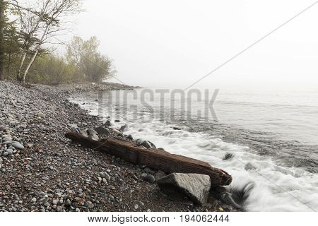 Lake Superior on a foggy day with rocky shore.