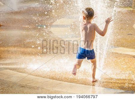 Cute happy Caucasian child running through the water stream of a sprinkler in the summer heat. Summer fun stock image.